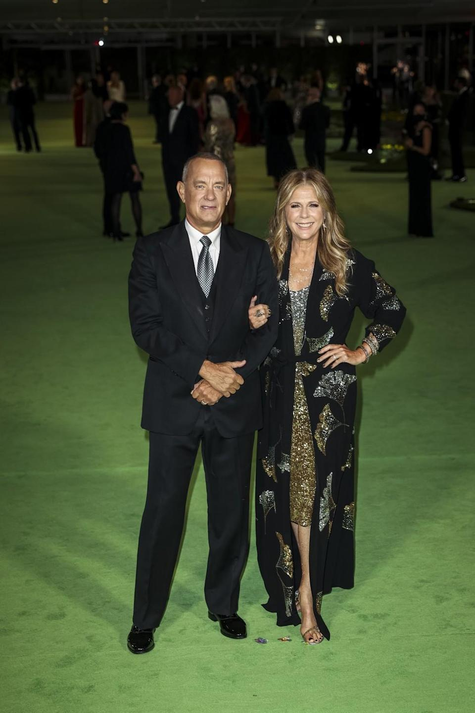 A man in a black suit and a woman in a sparkly gown posing on the green carpet
