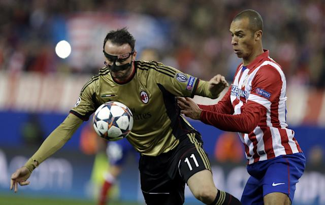 AC Milan's Giampaolo Pazzini, left, is challenged by Atletico's Miranda during a Champions League, round of 16, second leg, soccer match between Atletico Madrid and AC Milan at the Vicente Calderon stadium in Madrid, Tuesday March 11, 2014. (AP Photo/Paul White)