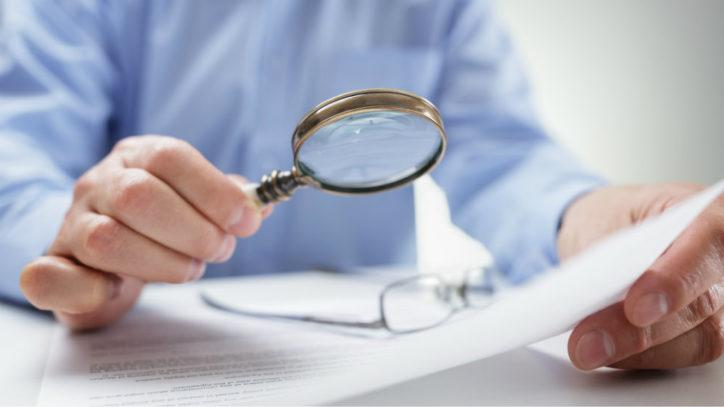 Man holding magnifying glass over a document
