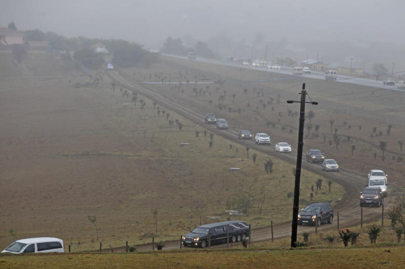 The hearse, foreground centre, carrying the remains of family members of former President Nelson Mandela drive to the grave site, with Nelson Mandela's house, at rear left, in Qunu, South Africa, Thursday, July 4, 2013. In a macabre family fed fought as Nelson Mandela remained in critical condition, a South African court ruled Wednesday that the former president's grandson must return the bodies of the 94-year-old's three deceased children to their original burial site. (AP Photo/Schalk van Zuydam)