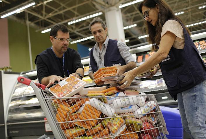 Workers of the Municipal Sanitary Surveillance confiscate hot dogs to be analzsed at a supermarket in Rio de Janeiro, Brazil, Monday, March 20, 2017. The European Union's spokesman in Brazil says the union is temporarily halting some imports of Brazilian meat amid an investigation into a massive scheme of meat adulteration, which involved some of the country's largest producers. (AP Photo/Silvia Izquierdo)