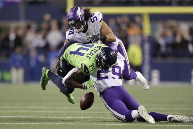 Seattle Seahawks' DK Metcalf (14) fumbles while being hit by Minnesota Vikings' Xavier Rhodes (29) and Eric Kendricks (54) during the second half of an NFL football game, Monday, Dec. 2, 2019, in Seattle. The Vikings' recovered on the play. (AP Photo/John Froschauer)