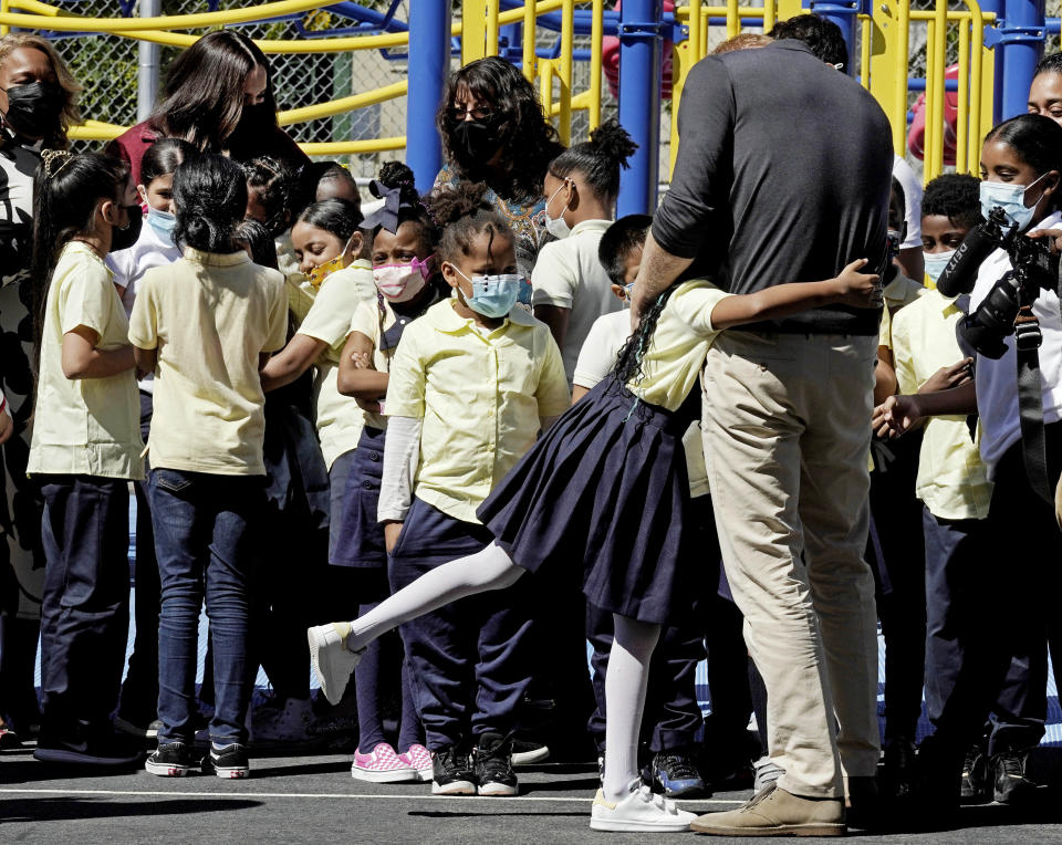 Meghan, the Duchess of Sussex, background left, and Prince Harry, foreground right, interact with students during their visit to P.S. 123, the Mahalia Jackson School, in New York's Harlem neighborhood, Friday, Sept. 24, 2021. (AP Photo/Richard Drew)