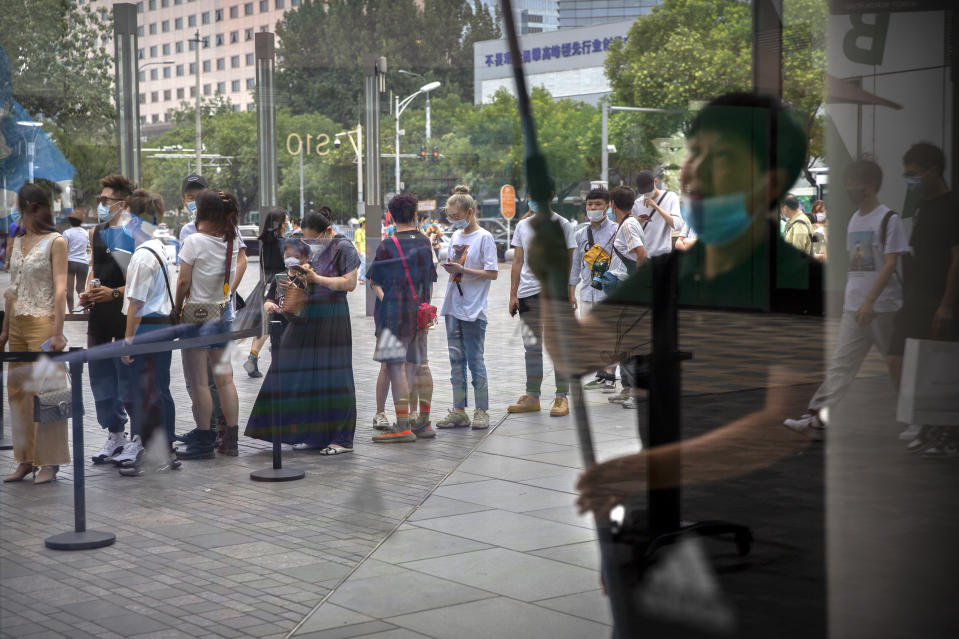 People wearing face masks to protect against the new coronavirus wait to show the results of a smartphone health check app before they can enter an outdoor shopping mall in Beijing, Saturday, July 4, 2020. China reported a single new case of coronavirus in Beijing on Saturday, plus a few more cases elsewhere believed to have come from abroad. (AP Photo/Mark Schiefelbein)