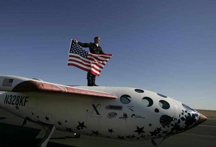 astronaut stands on top of SpaceShip One holding American flag