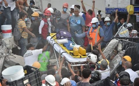 Rescuers, firefighters, policemen, soldiers and volunteers remove rubble and debris from a flattened building - Credit: AFP PHOTO / YURI CORTEZ