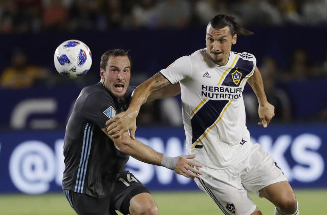 FILE 0 In this Aug. 11, 2018 file photo, LA Galaxy forward Zlatan Ibrahimovic, right, is defended by Minnesota United defender Brent Kallman during the first half of an MLS soccer match, in Carson, Calif. Ibrahimovic will remain at the Los Angeles Galaxy after the Major League Soccer club agreed with his requests, according to AC Milan sporting director Leonardo, Sunday, Dec. 9, 2018. (AP Photo/Marcio Jose Sanchez, file)