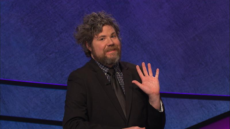 "In this undated handout photo provided by Jeopardy Productions, Inc., Austin Rogers waves during a taping of ""Jeopardy!"" in Culver City, Calif. Rogers, a New York City bartender, extended his run of wins to eight on the show that aired Oct. 5, 2017, and boosted his total winnings to more than $300,000. Rogers' on-screen antics are winning him a cult following. (Jeopardy Productions, Inc. via AP)"