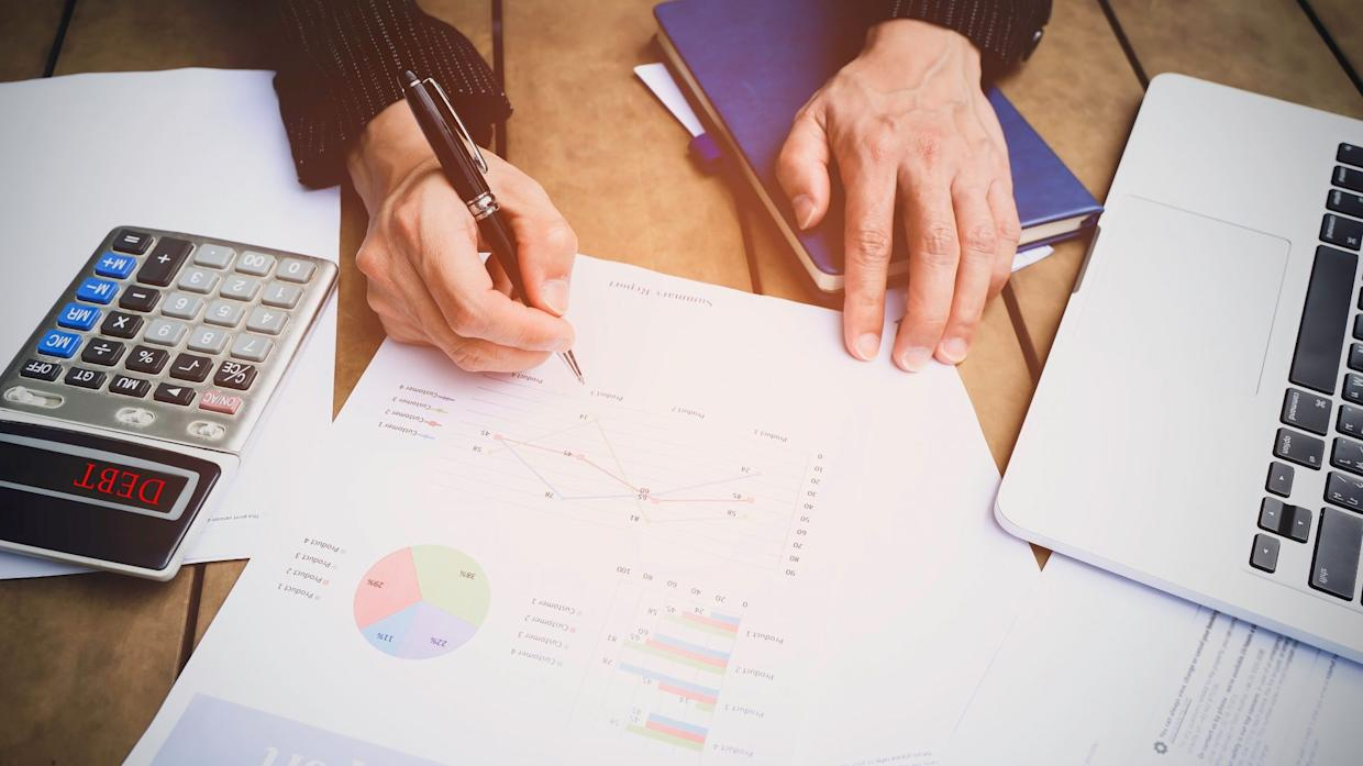 Selective focus man hand with pen check calculating the monthly of debt bills bank as a papers graph documents expenses and payment in the office.