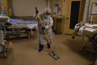 Hospital worker Alma Garibay mops the floor of a COVID-19 unit at Providence Holy Cross Medical Center in the Mission Hills section of Los Angeles, Tuesday, Dec. 22, 2020. (AP Photo/Jae C. Hong)