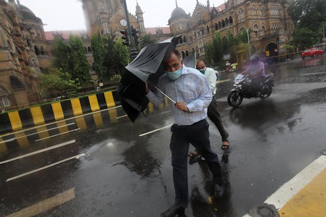 """People hold umbrellas during a thunderstorm and heavy rains in Mumbai, India on June 03, 2020. Tropical cyclone storm """"Nisarga"""" expected to hit the Maharashtra coast on Wednesday as per media report. (Photo by Himanshu Bhatt/NurPhoto via Getty Images)"""