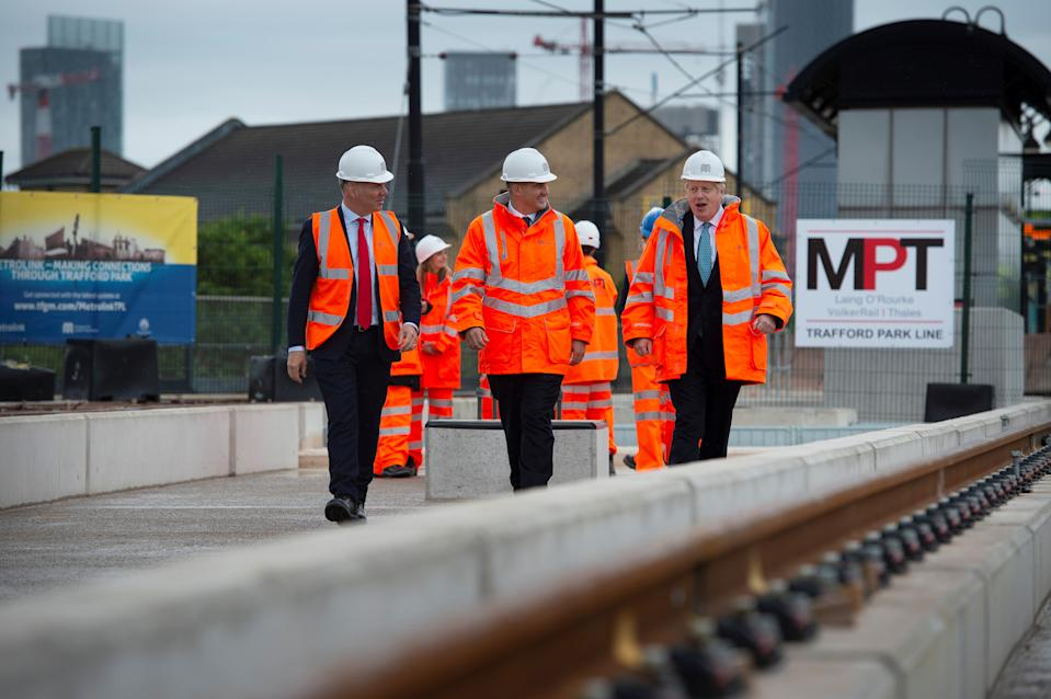 Britain's Prime Minister Boris Johnson walks with CEO of Transport for the North, Barry White and Britain's Northern Powerhouse Minister, Jake Berry as he visits the site of an under-construction tramline in Stretford, near Manchester, Britain July 27, 2019. Geoff Pugh/Pool via REUTERS