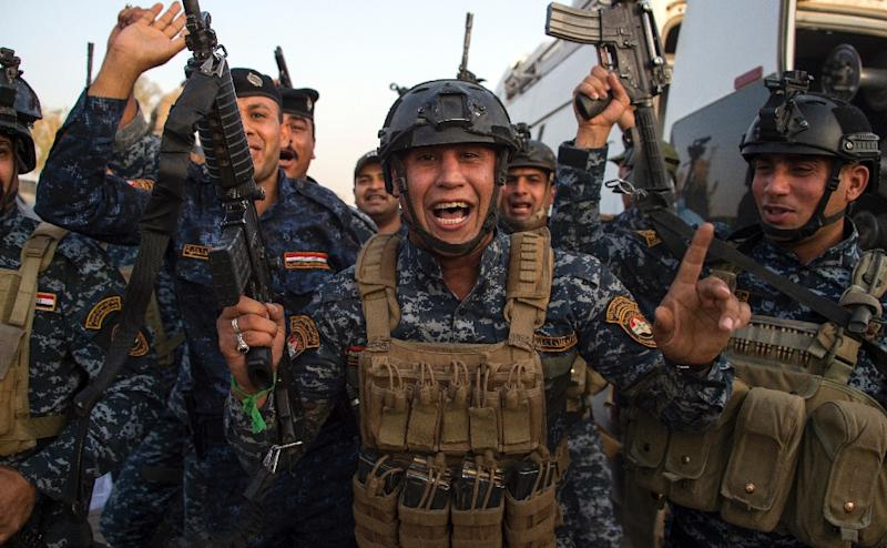 """Members of the Iraqi federal police forces celebrate in the Old City of Mosul on July 10, 2017 after the government's announcement of the """"liberation"""" of the embattled city"""