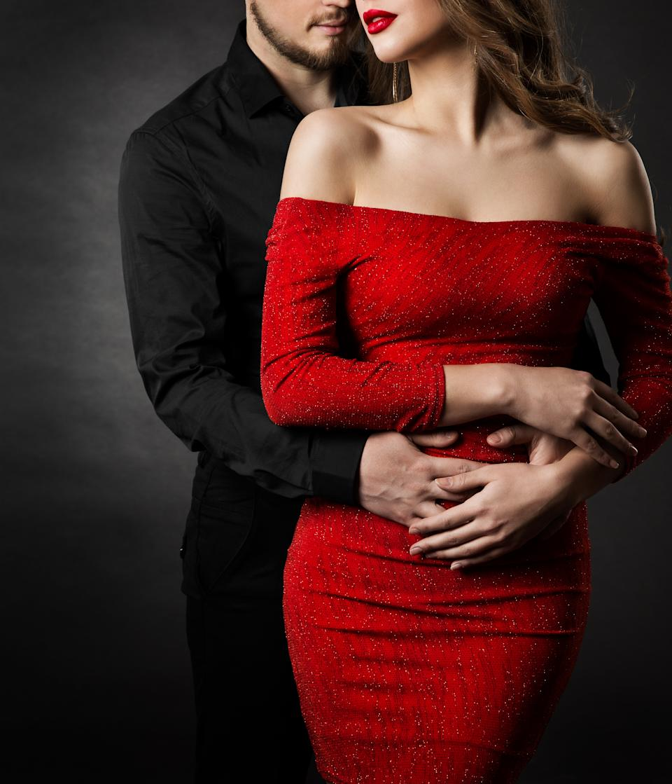 Man in black embracing Young Woman in Sexy Red Dress