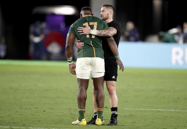 New Zealand's TJ Perenara embraces South Africa's Tendai Mtawarira following their Rugby World Cup Pool B game at International Stadium between New Zealand and South Africa in Yokohama, Japan, Saturday, Sept. 21, 2019. New Zealand defeated South Africa 23-13. (AP Photo/Jae Hong)