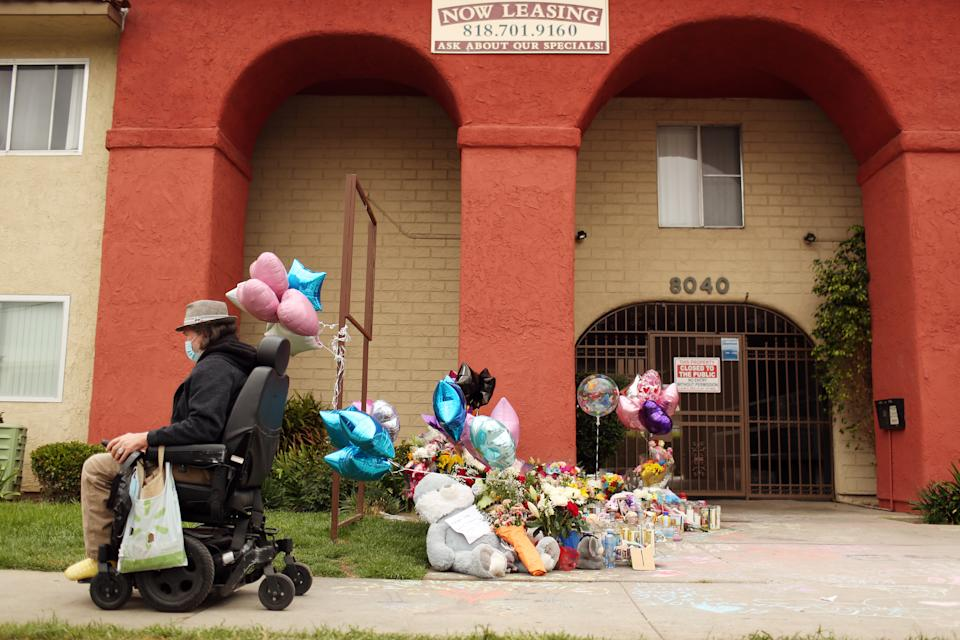 A passerby goes past a memorial outside the apartment where three young children were killed Saturday morning in San Fernando.