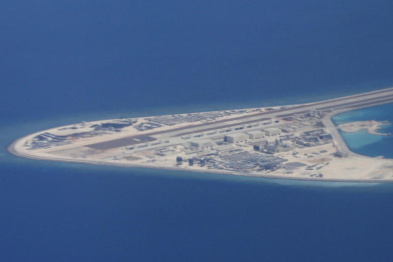 FILE - In this Friday, April 21, 2017, file photo, an airstrip, structures, and buildings on China's man-made Subi Reef in the Spratly chain of islands in the South China Sea are seen from a Philippine Air Force C-130 transport plane of the Philippine Air Force. A Chinese naval officer says China may further fortify man-made islands in the South China Sea depending on threats faced by the outposts. Navy academy researcher Senior Capt. Zhang Junshe last week repeated China's stance that it has the legal right to take whatever measures it deems appropriate on the islands in the South China Sea, which China claims virtually in its entirety. (AP Photo/Bullit Marquez, File)