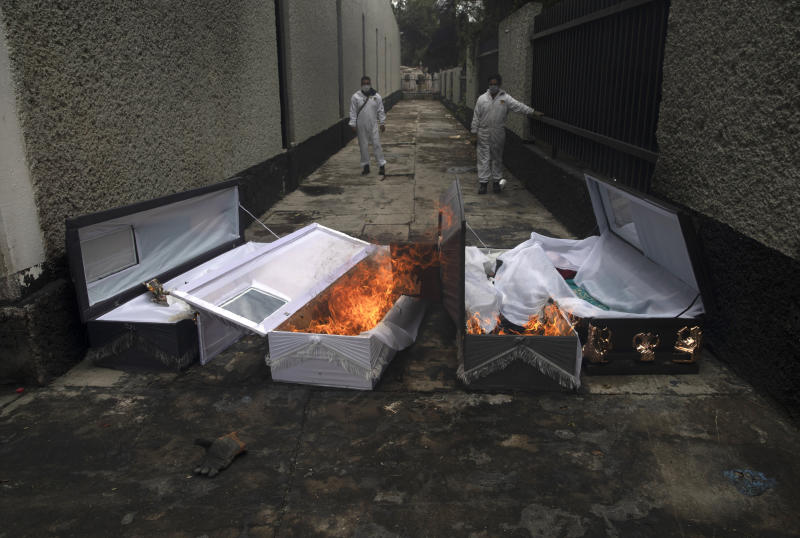 Crematorium workers burn the coffins of COVID-19 victims after they have been cremated at the San Nicolas Tolentino cemetery in the Iztapalapa neighborhood of Mexico City, Wednesday, June 24, 2020. (AP Photo/Marco Ugarte)