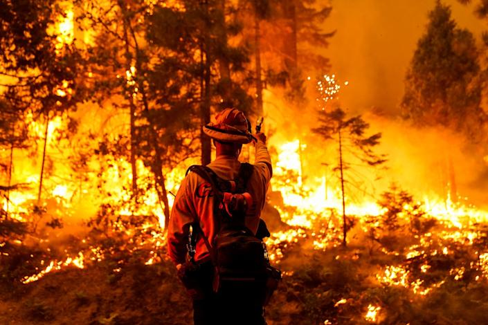 """A firefighter is silhouetted against the flames of the Creek fire as it approaches the Shaver Lake Marina on Sunday, Sept. 6, 2020. <span class=""""copyright"""">(Kent Nishimura / Los Angeles Times)</span>"""