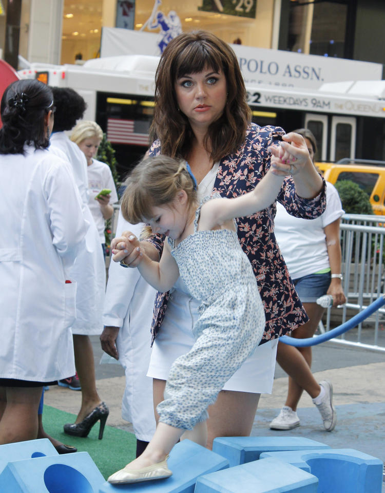 Tiffani Thiessen provided a helpful hand to her daughter, Harper, who exhibited her climbing skills at a Doc McStuffins event outside the Disney Store in Manhattan's Times Square. (8/21/2013)