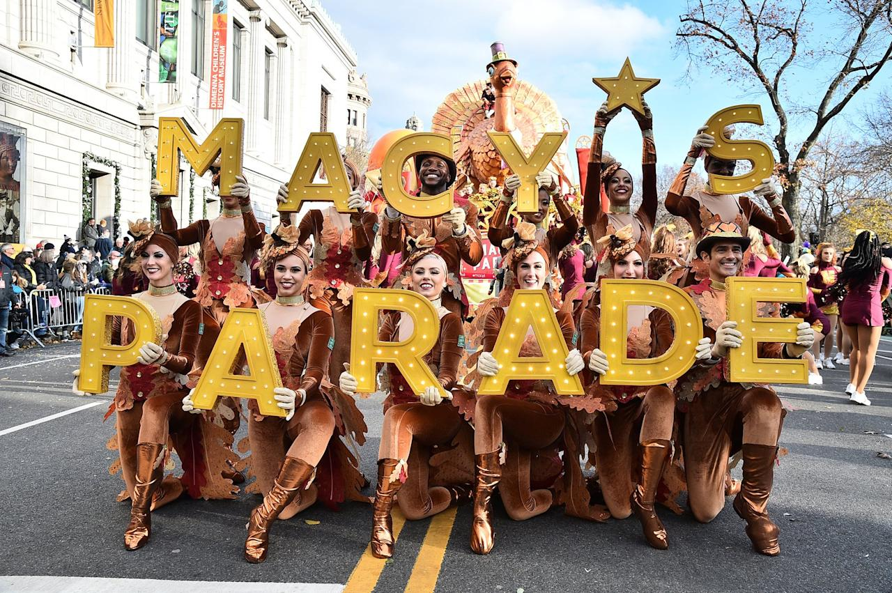 """Dancers dressed in fall colors and held up letters that spelled out """"Macy's Parade"""" in N.Y.C.'s Manhattan neighborhood."""