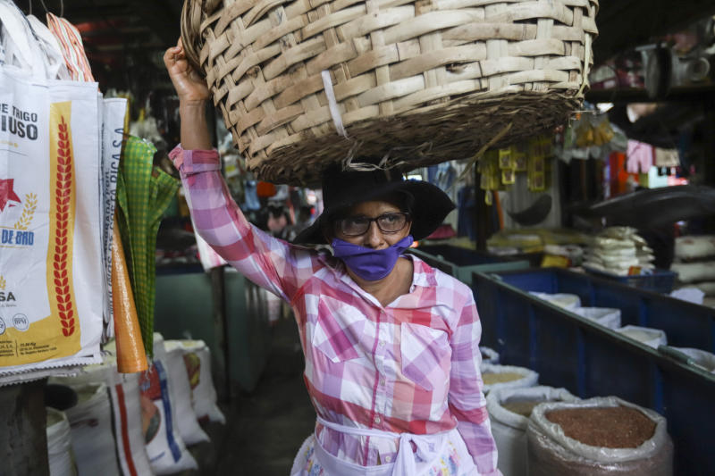 A fruit vendor, wearing a protective face mask, makes her way through a popular market in Managua, Nicaragua, Tuesday, April 7, 2020. Restaurants are empty, there's little traffic in the streets and beach tourists are sparse headed into Holy Week despite the government's encouragement for Nicaraguans to go about their normal lives. (AP Photo/Alfredo Zuniga)