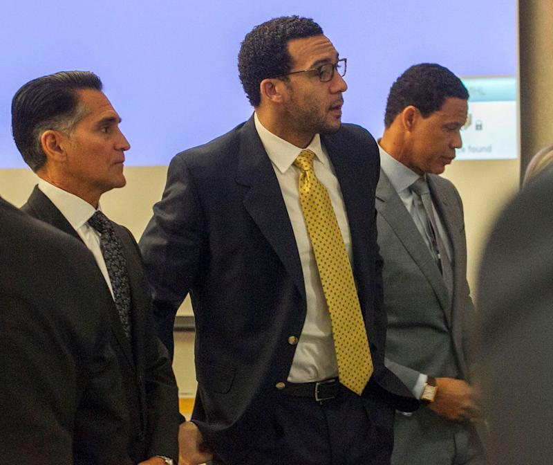 Former NFL football player Kellen Winslow Jr., center, stands as the jury enters the courtroom on the first day of his rape trial, Monday May 20, 2019, in Vista, Calif. Winslow's attorneys Brian Watkins, right, and Marc Carlo, left, flank him. (John Gibbins/The San Diego Union-Tribune via AP, Pool)