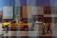 Municipal workers and storefronts along Main Street in downtown Galesburg, Ill., are reflected in a storefront window Thursday, June 17, 2021. A edifice from more prosperous days, the Orpheum Theater near the remodeled Amtrak station anchors one end of a downtown lined with banks, antique shops, eateries and empty storefronts. The bronze likeness of native poet Carl Sandburg stands watch at the other end. (AP Photo/Shafkat Anowar)