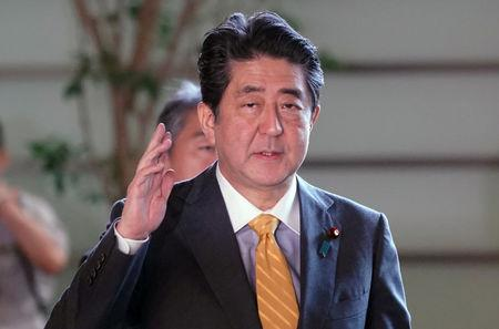 FILE PHOTO:  Japanese Prime Minister Shinzo Abe waves to media upon his arrival at his official residence in Tokyo