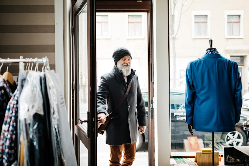 A mature man with a beard entering a menswear store.