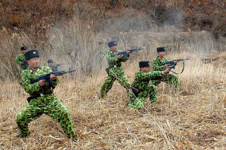 North Korean soldiers with weapons attend military training in an undisclosed location. REUTERS/KCNA