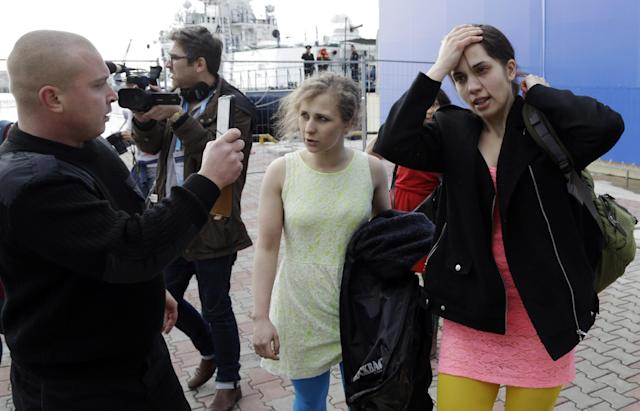 A Russian security officer records members of the punk group Pussy Riot Nadezhda Tolokonnikova, right, and Maria Alekhina, center, after they were attacked by Cossack militia in Sochi, Russia, on Wednesday, Feb. 19, 2014. Cossack militia attacked the Pussy Riot punk group with horsewhips on Wednesday as the group tried to perform under a sign advertising the Sochi Olympics. (AP Photo/Morry Gash)