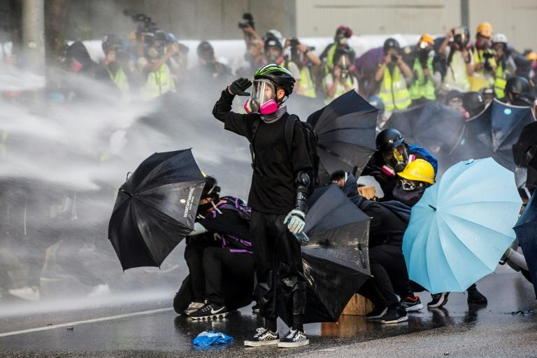 Protesters react as police fire water cannons outside the government headquarters in Hong Kong