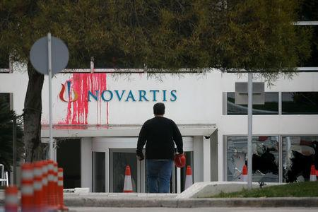 A worker walks in front the entrance of the Swiss drugmaker Novartis offices after protesters threw paint and smashed windows, in Athens, Greece, February 25, 2018. REUTERS/Costas Baltas