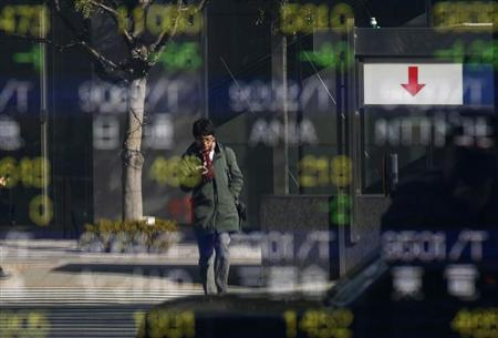 A man is reflected in a stock quotation board outside a brokerage in Tokyo