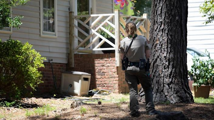A officer carefully approaches the porch where a cobra was spotted. Law enforcement has blocked off Sandringham Drive as animal control officers continue to search for a missing cobra on June 30, 2021.