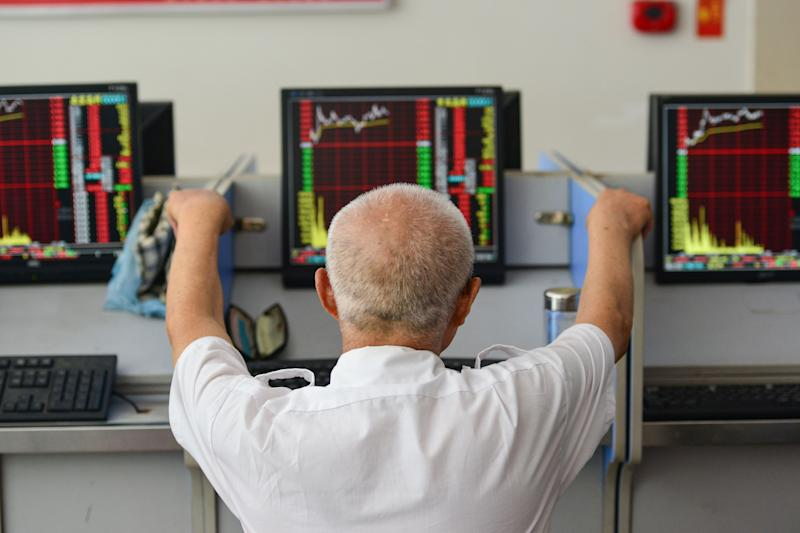 An investor looks at screens showing stock market movements at a securities company in Fuyang in China's eastern Anhui province on July 6, 2020. - Shanghai stocks surged on July 6 to a more than two-year high as investors piled in following a combination of rosy predictions for the market and strong economic data. (Photo by STR / AFP) / China OUT (Photo by STR/AFP via Getty Images)