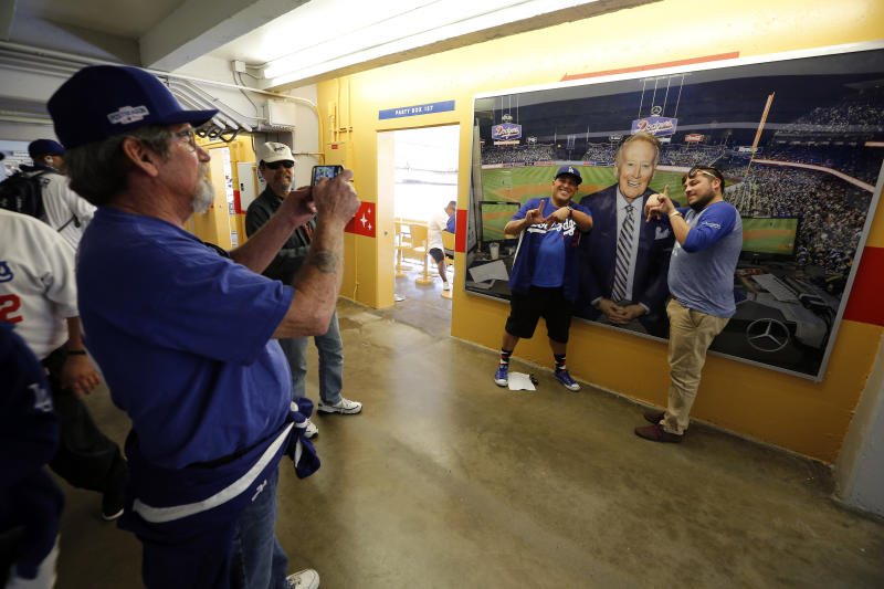 Baseball fans pose for a picture in front of a photo of Vin Scully before the start of an opening day baseball game between the Los Angeles Dodgers and the San Diego Padres, Monday, April 3, 2017, in Los Angeles. (AP Photo/Ryan Kang)