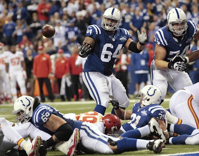 Indianapolis Colts' Donald Brown (31) fumbles before the Colts' Andrew Luck (12) recovered the football and went in for a five-yard touchdown during the second half of an NFL wild-card playoff football game Saturday, Jan. 4, 2014, in Indianapolis. (AP Photo/AJ Mast)