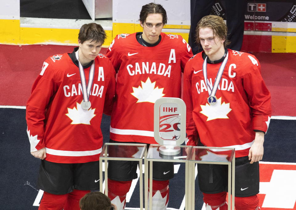 Canada's Connor McMichael (17), Dylan Cozens (22) and Bowen Byram (4) pose with their silver medals and trophy after the team's loss to the United States in the championship game in the IIHF World Junior Hockey Championship, Tuesday, Jan. 5, 2021, in Edmonton, Alberta. (Jason Franson/The Canadian Press via AP)