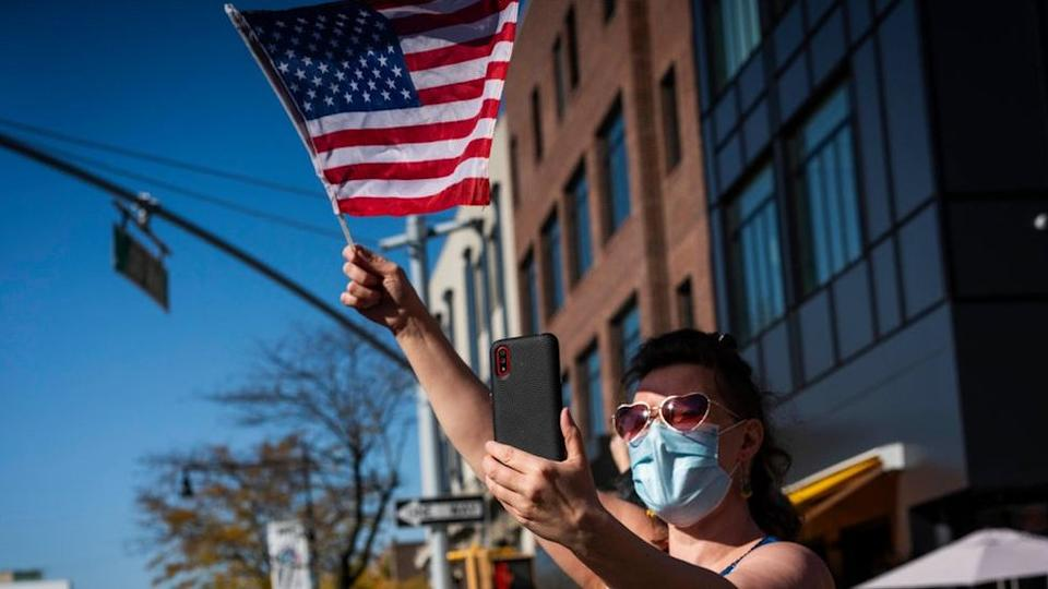 A woman waves an American flag during a celebration in Astoria