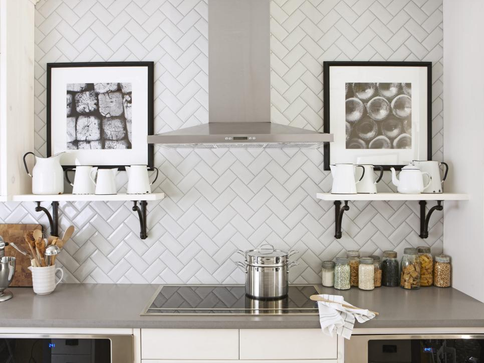 """<p>One of the easiest ways to mix up your kitchen's backsplash design is by laying tile in a fun, unexpected pattern, such as this herringbone design featured in <i><a href=""""http://www.hgtv.com/design/packages/hgtv-magazine?oc=PTNR-YahooRealEstate-HGTV-subway_tile_twists"""">HGTV Magazine</a></i>. By pairing the design with simple shelves and black-and-white art, the charming tilework remains the star of the space. <i>Photo by Stacey Brandford. </i></p>"""