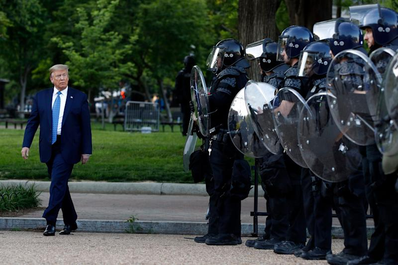 President Donald Trump walks past police in Lafayette Park after he visited St. John's Church across from the White House on June 1. Part of the church was set on fire during protests the night before.