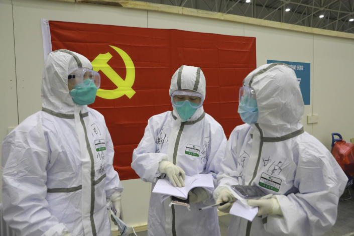 "In this photo taken Feb. 8, 2020 and released by Xinhua News Agency, medical workers discuss patients' treatment near a Communist Party flag at the ""Wuhan Living Room"" temporary hospital in Wuhan, central China's Hubei Province. As the rest of the world grapples with a burgeoning virus outbreak, China's ruling Communist Party has turned to its propaganda playbook to portray its leader as firmly in charge, leading an army of health workers in a ""people's war"" against the disease. (Gao Xiang/Xinhua via AP)"