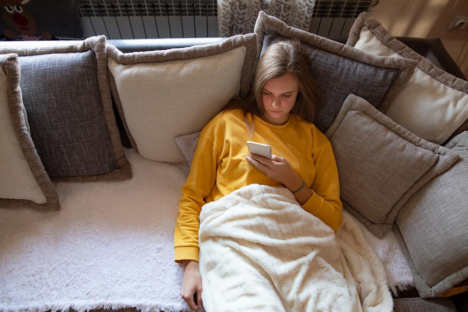 Young woman using mobile phone on sofa in the morning