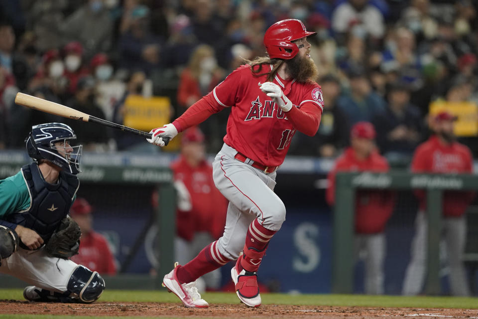 Los Angeles Angels' Brandon Marsh, right, and Seattle Mariners catcher Tom Murphy watch Marsh's two-RBI double in the third inning of a baseball game, Friday, Oct. 1, 2021, in Seattle. Luis Rengifo and David Fletcher scored on the play. (AP Photo/Ted S. Warren)