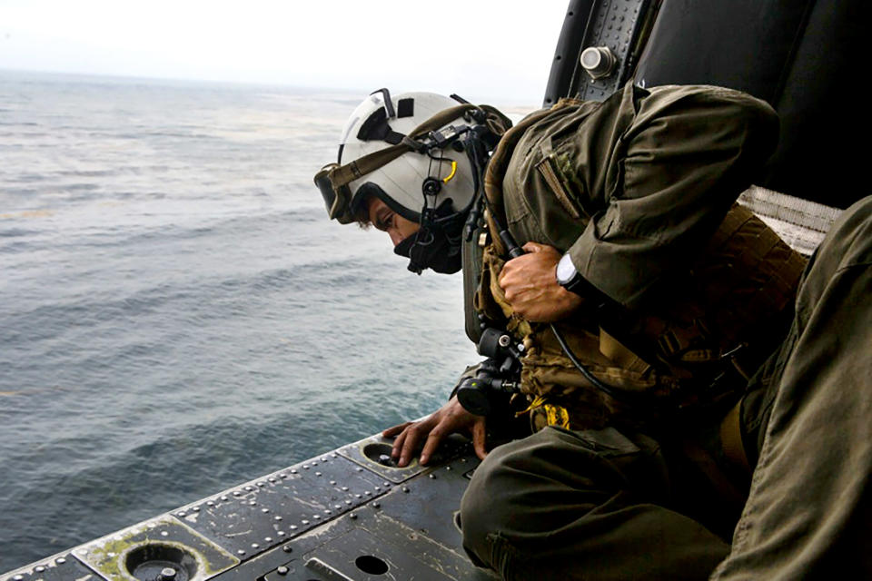FILE - In this July 30, 2020 file photo a Naval aircrewman, looks out of a U.S. Navy helicopter while conducting search and rescue relief operations following an assault amphibious vehicle mishap off the coast of Southern California. A U.S. Marine Corps commander was fired Tuesday, March 23, 2021, following an investigation into the sinking of an amphibious assault vehicle in the ocean off Southern California that killed nine service members last year. (Lance Cpl. Mackenzie Binion/U.S. Marine Corps via AP,File)