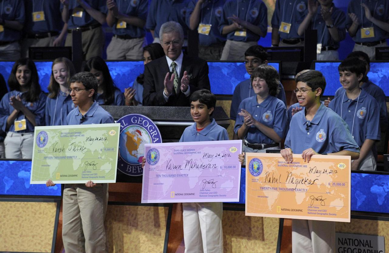 National Geographic Bee host Alex Trebek, rear center, and others, applaud the National Geographic Bee top winners, from left, Vansh Jain, from Minocqua-Hazel-hurst-Lake Tomahawk Elementary School in Minocqua, Wis.; Varun Mahadevan, from Prince of Peace Christian School in Fremont, Calif.; and champion Rahul Nagvekar, 14, from Quail Valley Middle School in Missouri City, Texas., Thursday, May 24, 2012, in Washington. (AP Photo/Susan Walsh)