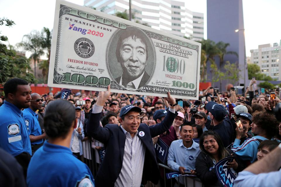 U.S. Democratic presidential candidate Andrew Yang hoists a supporter's sign after speaking at a rally in downtown Los Angeles, California, U.S., April 22, 2019. REUTERS/Lucy Nicholson     TPX IMAGES OF THE DAY