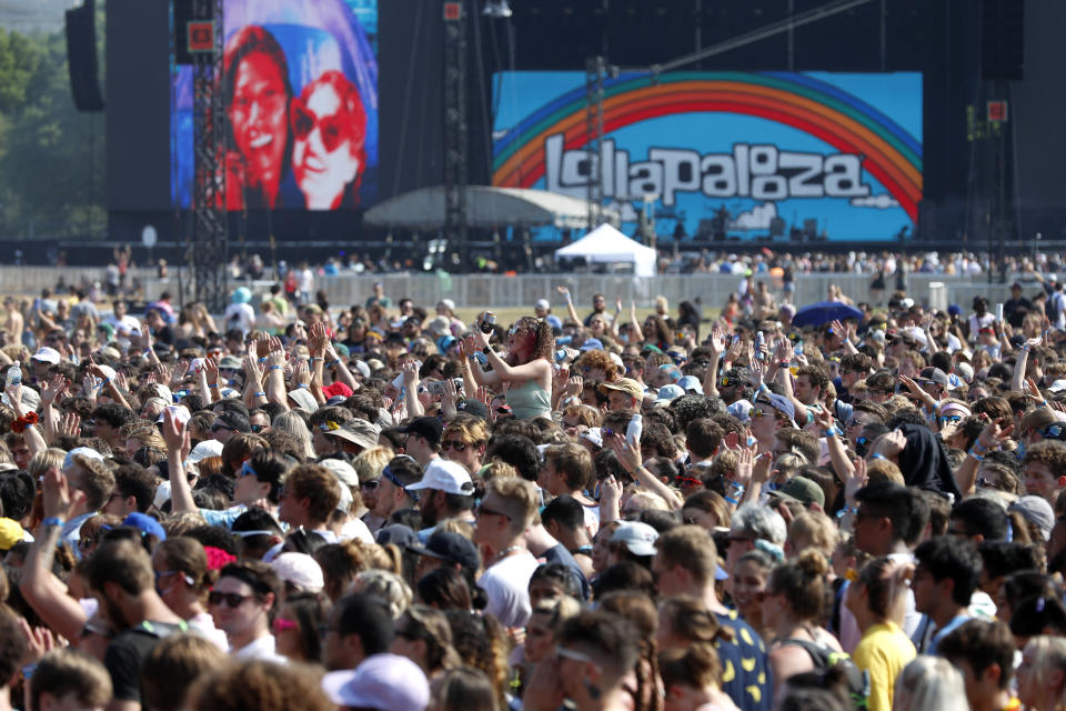 FILE - In this July 29, 2021 file photo, fans gather and cheer on day one of the Lollapalooza music festival at Grant Park in Chicago. Illinois dispensaries sold a record $127.8 million in recreational marijuana in July, with a big boost coming from out-of-state fans who converged on Chicago for the Lollapalooza music festival. (AP Photo/Shafkat Anowar File)